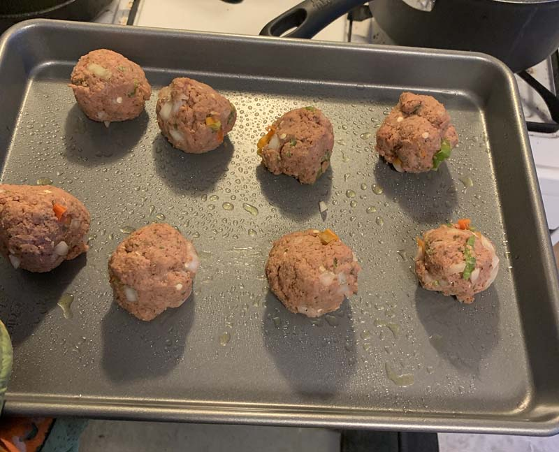 photo of meatballs on a baking sheet before cooking