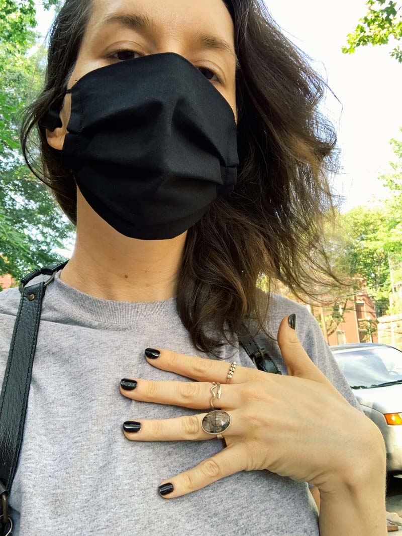a photo of me outside with a black mask on, gray t-shirt and black nails freshly painted