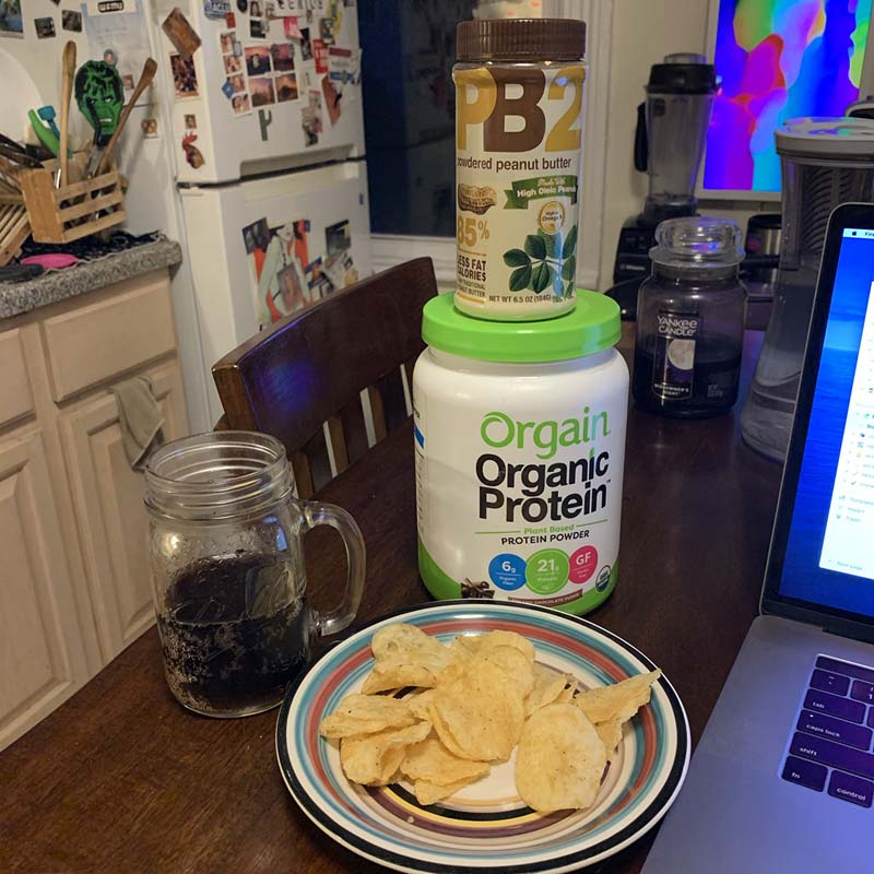 a glass of coke zero and a plate with chips in front of a cannister of protein powder and peanut butter powder