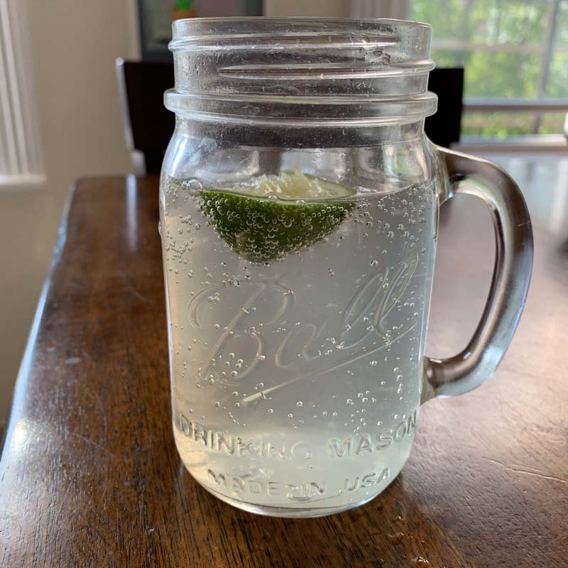 a mason jar with a fizzy drink and lime on a brown kitchen table