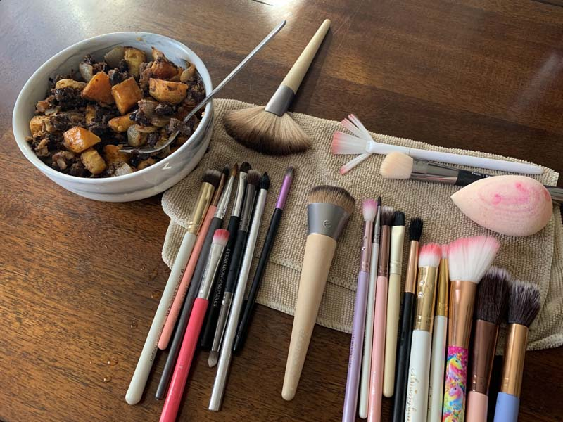 photo of a table with makeup brushes drying on a small towel and a bowl of sweet potatoes and black beans next to it